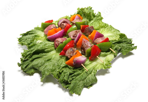 Three colorful kabobs over a bed of lettuce