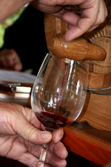 Red wine being poured in to a wine glass from a small barrel