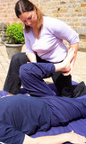 Assisted leg stretch as part of a Thai body massage. poster