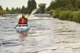 Female kayaker paddling on River Dee in Wales  poster
