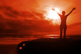 Fiery glory - woman with arms raised on sunset seascape poster