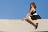 beauty girl sit on concrete billboard on blue sky poster