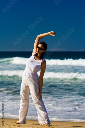 Young woman exercising on the tropical beach