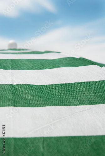 poster of Stripped sunshade umbrella and blue sky