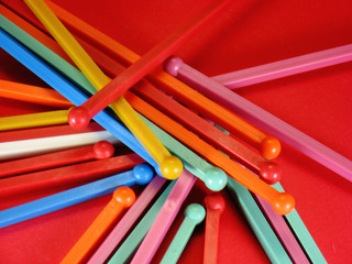 many colored cocktail type stirrers on a red background