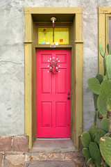 Adobe house doorway with pink colorful door