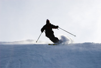 Mountain-skier sliding on the flank of hill