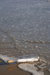 Message in a bottle being washed up onto the shore