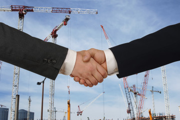 Two men shaking hands in front of a major construction site