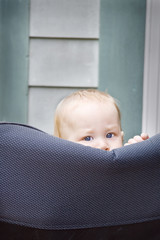 Curious baby boy peeking over a chair