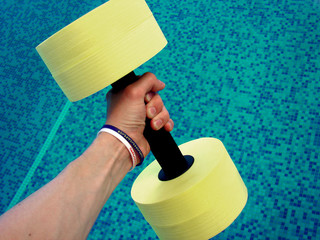 hand with wristbands holds yellow dumbbell for aqua aerobics