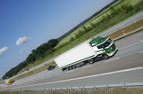 clean green truck speeding past poster