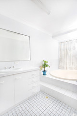 Brightly lit airy bathroom with white tiles