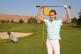 A pretty woman golfer retrieving her ball from the hole poster