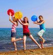 Three girls with colorful beach balls walking on sea shore
