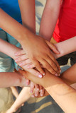 Hands of diverse group of teenagers joined in union poster
