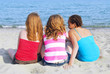 Portrait of three teenage girls sitting on a sandy beach