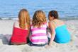 Portrait of three teenage girls sitting on a sandy beach
