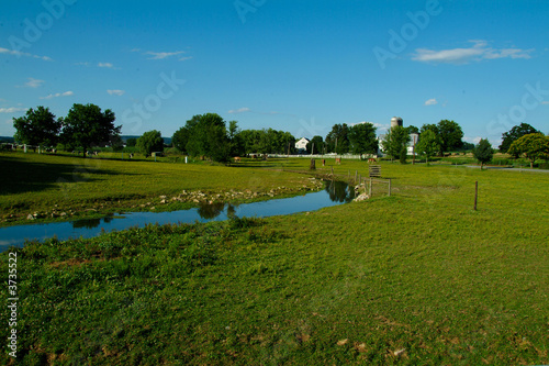 Horse Farm in Lancaster PA with brook in foreground and blue sky