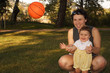 A mother with nine month old daughter with a ball.