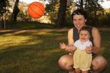 A mother with nine month old daughter with a ball. poster