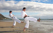 Young adult men practicing a Kata on the beach