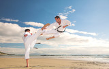 Young adult men practicing Karate on the beach
