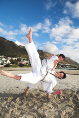 Young adult men with black belt practicing karate on the beach