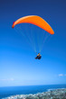 Paraglider launching from the ridge with an orange canopy