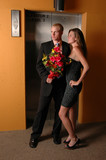 A romantic young couple waiting at the elevator poster