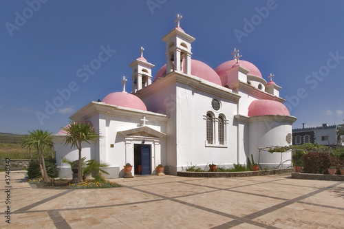 poster of  Orthodox church on coast of lake Tiberias, shined by the sun.