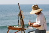 Painter at the Seaside, sitting at Easel working a Painting poster