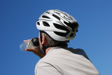 Thirsty man in helmet drinking water from sports bottle. poster