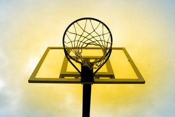 yellow basketball hoop against the blue sky.