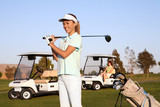 A pretty woman golfer ready to hit on the fairway poster