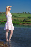woman stand in river and to look into the distance poster