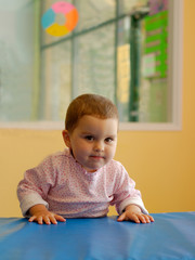 An infant girl in a gym - a lot of determination in her face.
