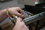 Engineer tests fiber-optic link by the reflectometer poster