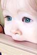 Little Baby biting on crib, taken closeup with green eyes