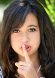 A pretty teenage girl doing be quiet gesture poster