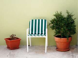 Terracota flowerpots and an old white chair with striped pillow