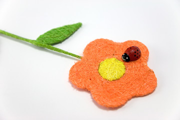 red wooden ladybird on an orange raffia flower
