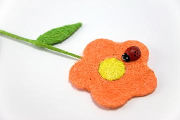 red wooden ladybird on an orange raffia flower