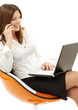 businesswoman with laptop and phone in orange chair over white