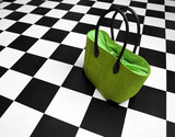 Green purse on black and white floor. Women handbag poster