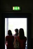 Three girls exit the building on exit door. Exit symbol poster