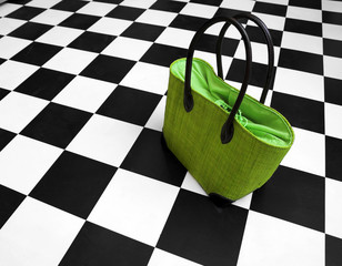 Green purse on black and white floor. Women handbag