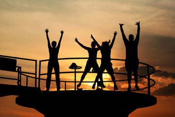 Happy people jumping silhouettes. Happiness concept