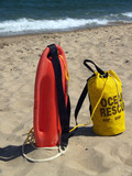 Ocean Rescue Gear in Sand-- Patrol Rescue Can and Rope Bag poster