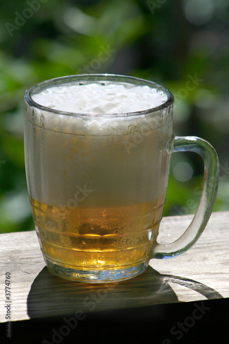 poster of Mug of beer with foam on a wooden board.